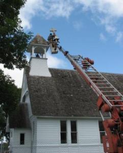 Steve Haeckel reinstalls the cross on St. Paul's.